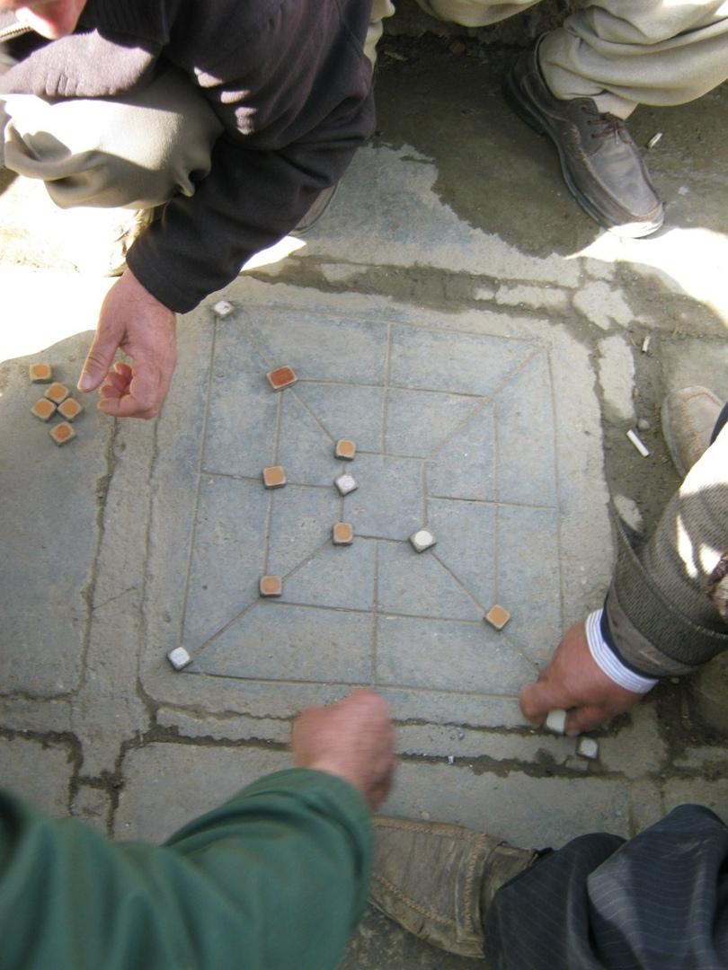 Игра в некую игру на тротуаре в городе Санандаж.