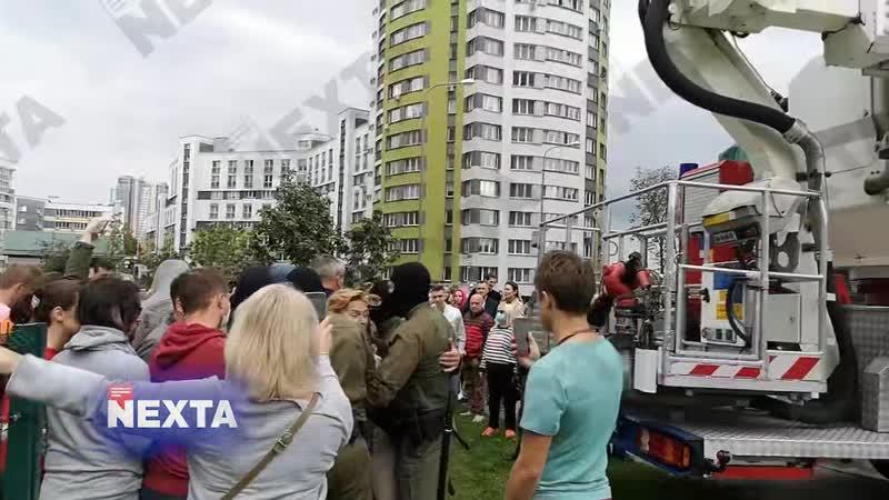 Люди держат руками кран чтобы пожарные не могли снять бело красно белый флаг